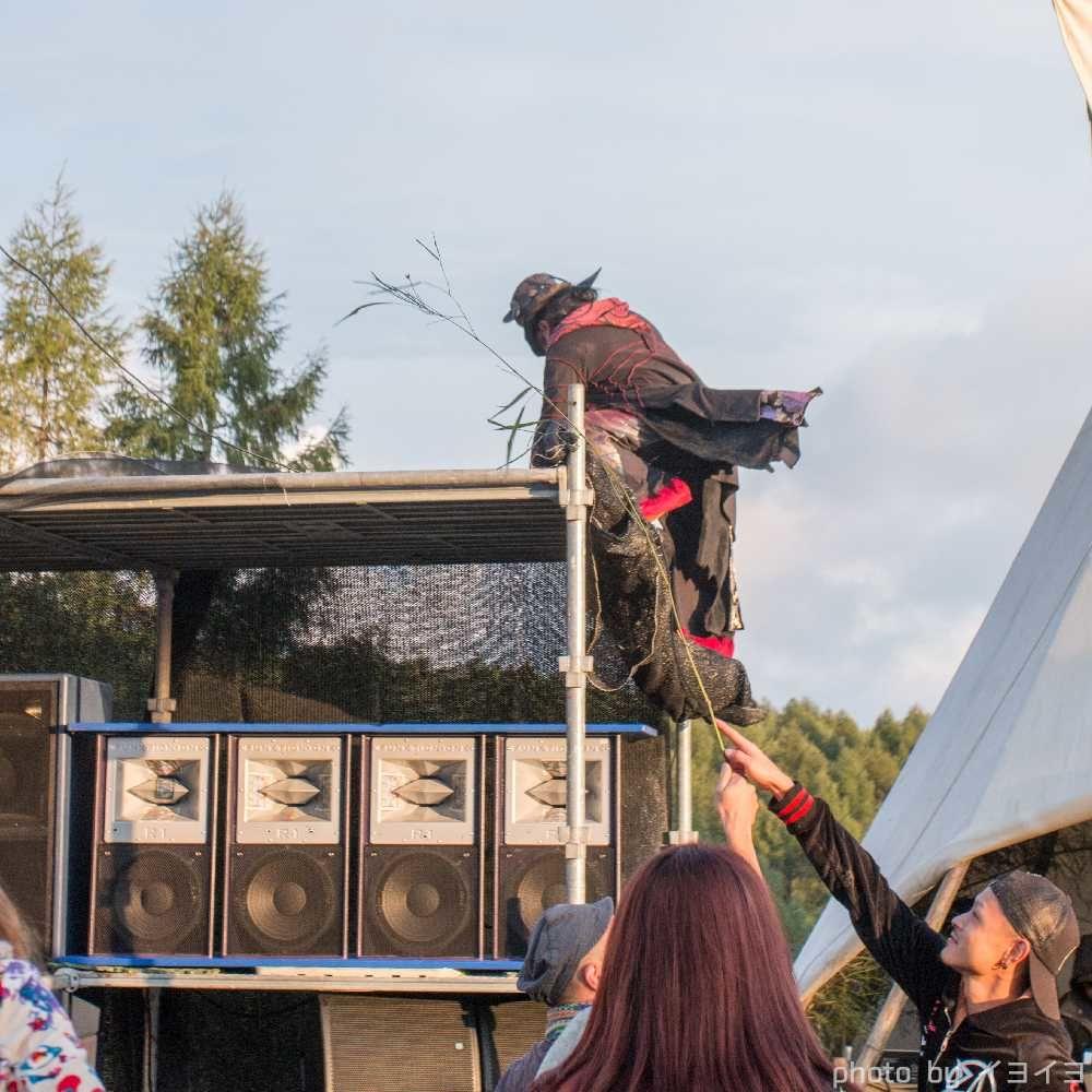 アウトドアフェス会場のスピーカーに上るパフォーマー